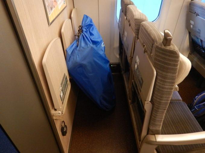 新幹線最後部の荷物起きスペースに輪行袋を置く